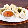 Siomay di atas piring dengan saus dan serbet merah